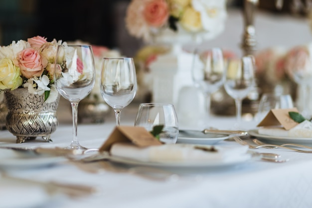 Beautiful table served with glassware and cultery, decorated with flowers, prepared for festive event.