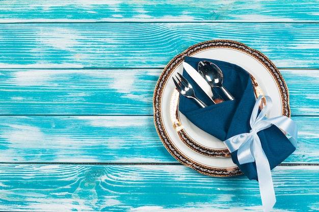 Beautiful table setting on blue wooden background