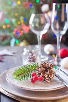 Beautiful table setting for christmas party celebration over a three with light toys