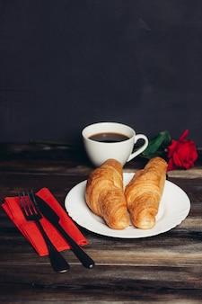朝食、クロワッサン、コーヒーのための美しいテーブルセッティング