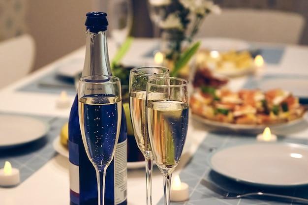 홈 파티를 위한 아름다운 테이블 세팅. 유리 제품, 양초, 샴페인과 함께하는 fne 식사.
