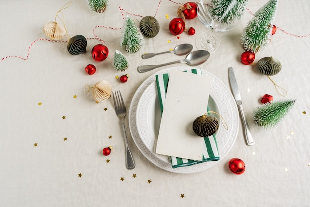 Beautiful table setting on grey background with white plates, glass, cutlery silverware and christmas decorations