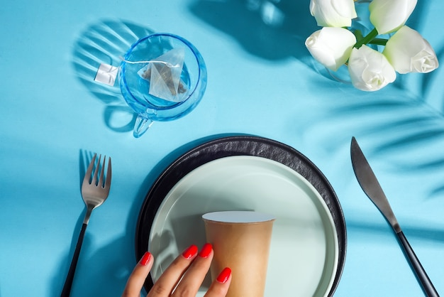 Beautiful table setting and paper cup on a plate.