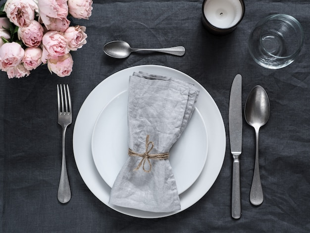 Beautiful table setting with pink spray roses and candle on gray linen tablecloth.