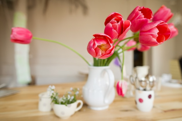 Beautiful table setting with red tulips, forget-me-not and cups on the wooden table.