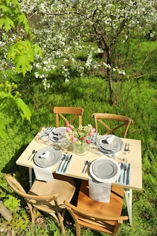 Beautiful table setting with vase of flowers in garden