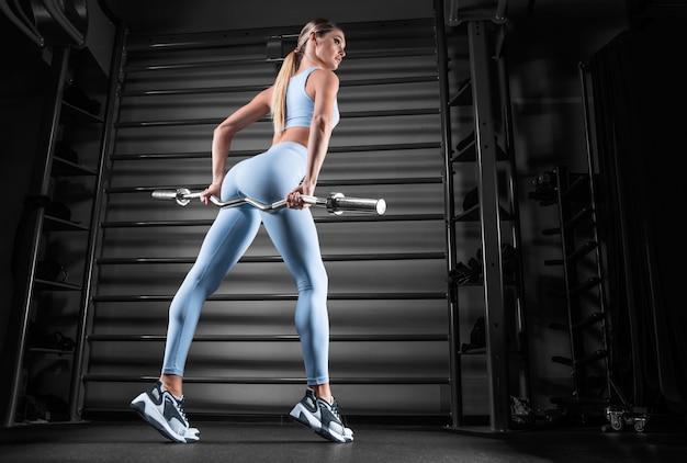벽 바의 배경에 대해 그녀의 손에 바 벨과 체육관에서 포즈를 취하는 아름 다운 키 금발. 스포츠, 피트니스, 에어로빅, 보디 빌딩, 스트레칭의 개념. 다시보기.