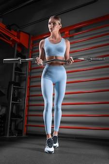 벽 바의 배경에 대해 그녀의 손에 바 벨과 체육관에서 포즈를 취하는 아름 다운 키 금발. 스포츠, 피트니스, 에어로빅, 보디 빌딩, 스트레칭의 개념. 전면보기.