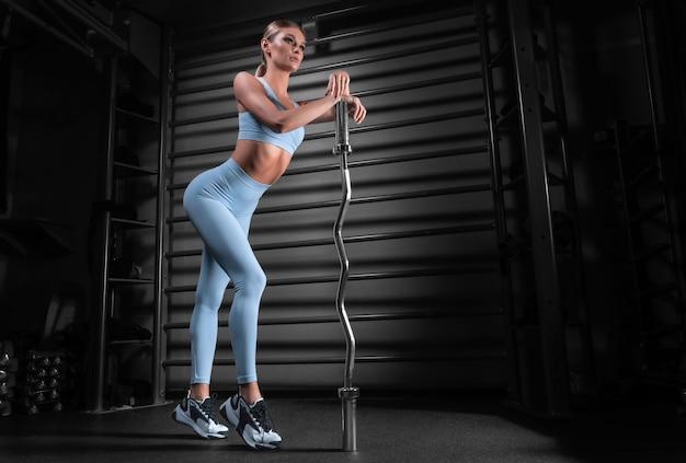 벽 바의 배경에 대해 그녀의 손에 바 벨과 체육관에서 포즈를 취하는 아름 다운 키 금발. 스포츠, 피트니스, 에어로빅, 보디 빌딩, 스트레칭의 개념. 측면보기.