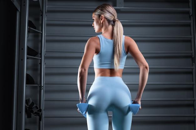 Красивая высокая блондинка позирует в тренажерном зале с гантелями в руках против штанги. вид сзади.