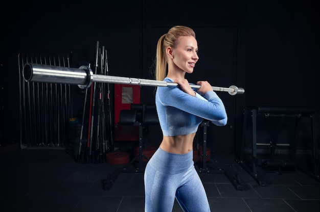 美しい背の高いブロンドは、彼女の肩にバーベルを持ってジムに立っています。フロントスクワット。フィットネスとボディービルのコンセプト。ミクストメディア