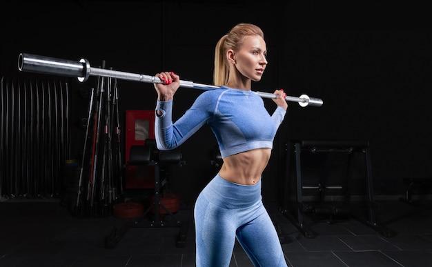 아름다운 키가 큰 금발은 그녀의 어깨에 바벨과 함께 체육관에 서 있습니다. 스쿼트. 피트니스 및 보디 빌딩 개념. 혼합 매체