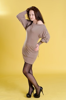 Красивая высокая женщина в бежевом платье позирует