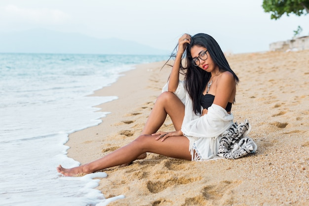Beautiful tan asian woman with red lips sitting on send near sea in white beach bohemian outfit stylish woman resting on tropical beach holidays and vacation concept