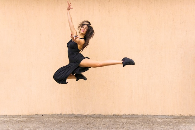 Beautiful tango dancer jumping in air against wall backdrop