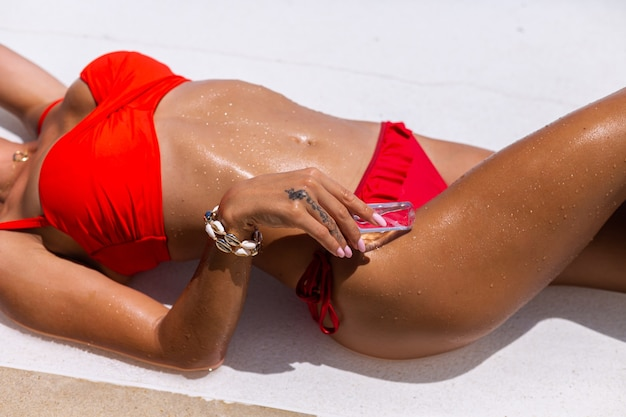 Beautiful tanned fit caucasian woman bronze shiny skin in bikini with coconut oil by blue swimming pool sunny day