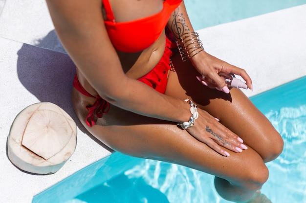 Beautiful tanned fit caucasian woman bronze shiny skin in bikini with coconut oil