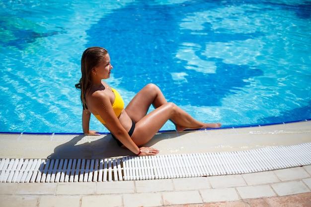 Красивая загорелая девушка в желтом купальнике в большом бассейне с голубой водой