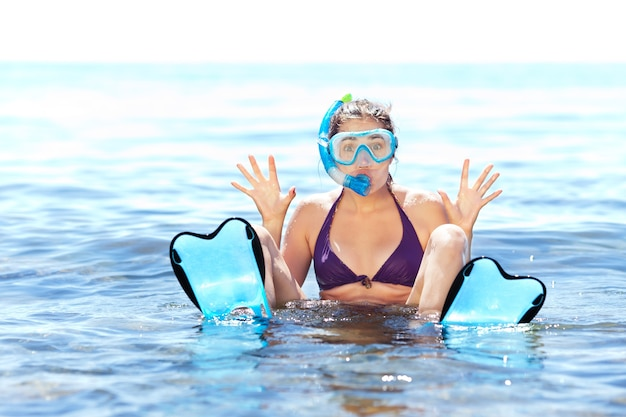 Beautiful tanned girl with snorkeling equipment having fun in shallow water