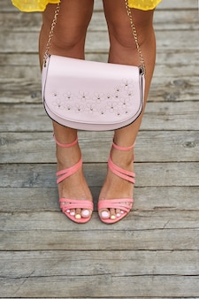 木の床に財布を持っているかかととコーラルサンダルの女の子の美しい日焼けした脚