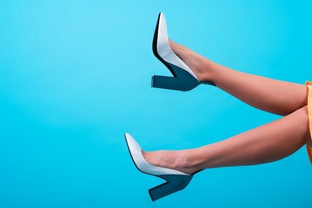 1톤 색상 배경에 발 뒤꿈치가 있는 세련되고 세련되고 고전적인 신발을 신은 어린 소녀의 아름답고 검게 그을린 다리. 프로모션 사진입니다. 텍스트를 위한 장소