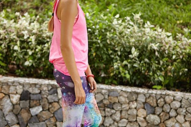 Красивая загорелая женщина-спортсменка в леггинсах с космическим принтом и розовой майке гуляет по дороге в городском парке, переводя дыхание после активных кардиоупражнений, готовится к марафону
