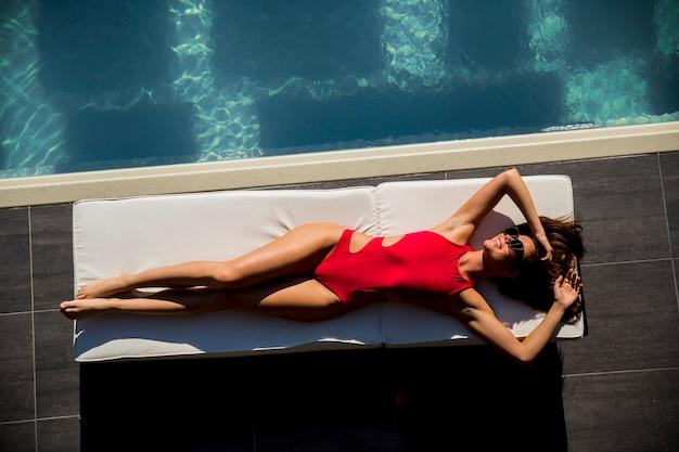 Beautiful tanned woman in red bikini relaxing near luxury swimming pool