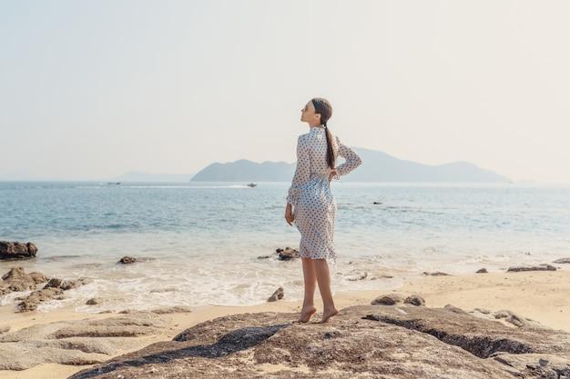 Beautiful tanned woman wearing white dress on the beach