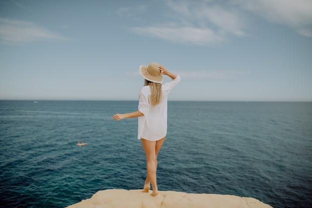 Красивая загорелая женщина с поднятыми руками, глядя на океан