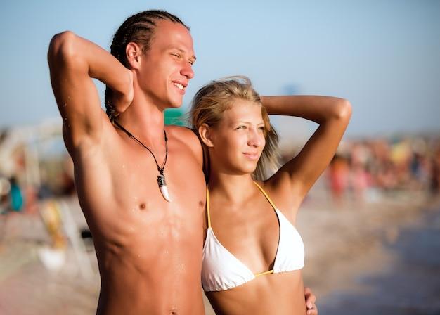 海の水の端に立って、ビーチを背景に晴れた夏の日に太陽の光を楽しんでいる美しい日焼けした若いカップル。休暇、旅行、アクティブな健康的なライフスタイルの概念
