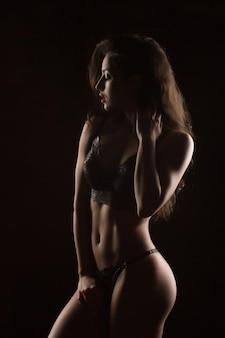 レースのランジェリーでポーズをとるセクシーな体を持つ美しい日焼けした若い女性。影と光