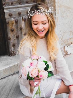 Beautiful tartar young wedding girl in wreath from beads with a bouquet of flowers. close up portrait of an attractive pretty modern bride holding roses bouquet. selective focus