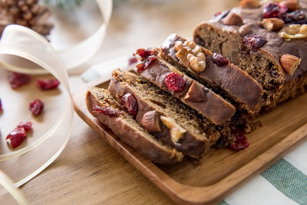 Beautiful tasty homemade mixed nut dried fruit cake on wooden table