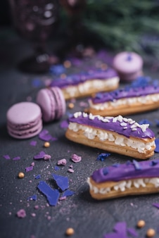 Beautiful and tasty purple eclairs and macaroons with lavender bouquet