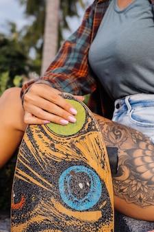 ジーンズのショートパンツ、格子縞のシャツの美しい入れ墨フィットの女性は、ロングボードを保持している日没の光で階段に座っています