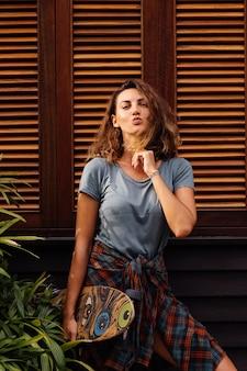 진 반바지에 아름 다운 문신 된 맞는 여자, longboard와 격자 무늬 셔츠