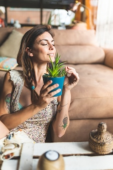 Beautiful tattooed woman holding plant at home.