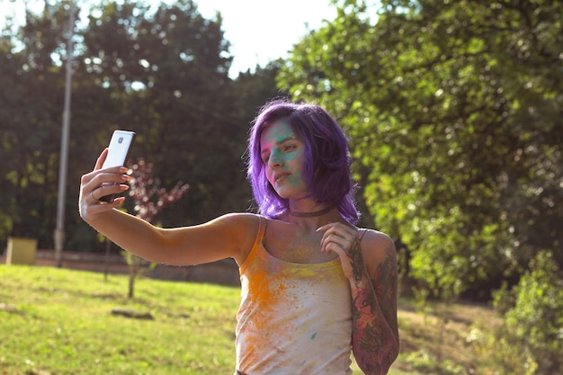ホーリー祭で自分撮りをしている紫色の髪の美しい入れ墨の若い女性