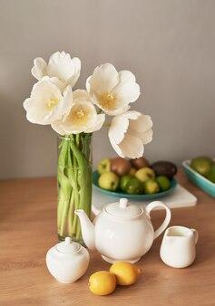 木製のテーブルに美しいお茶サービス。ホームインテリア、花瓶の花の花束、ティーポットのセットを持つテーブル。