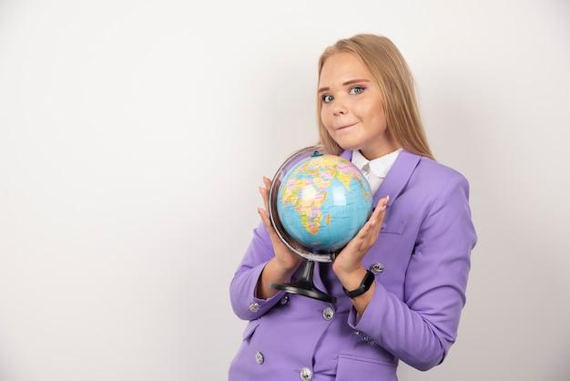 白い壁に地球儀を保持している美しい先生。