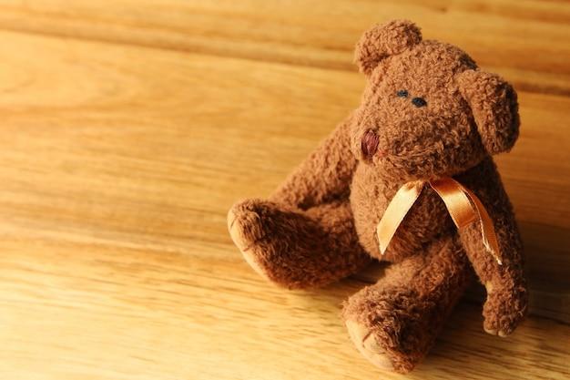 Красивый плюшевый мишка на деревянной поверхности