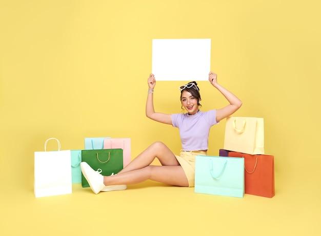 ショッピングバッグと一緒に座って、黄色の背景に手で空白のバナーを保持している美しい十代のアジアの女性の買い物客。