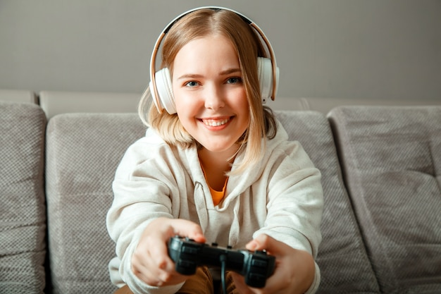 Красивая девушка-подросток блондинка играет в видео-консольную игру с помощью геймпада с джойстиком игрового контроллера, сидя на диване. счастливый молодой игрок женщины выигрывает в игровой консоли, играя в видеоигры на домашней вечеринке