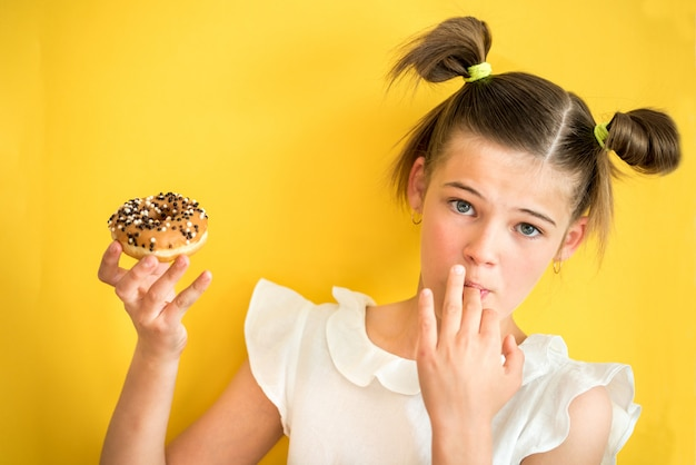 Beautiful teen girl eating a donut. emotionally laughing. on a yellow yak background. summer sunny picture
