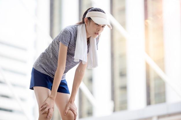 Красивая девушка упражнения в городе с полотенцем на шее
