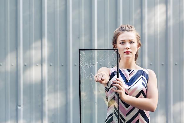 Красивая девочка-подросток, держа в руках битое стекло. концепция феминизма.