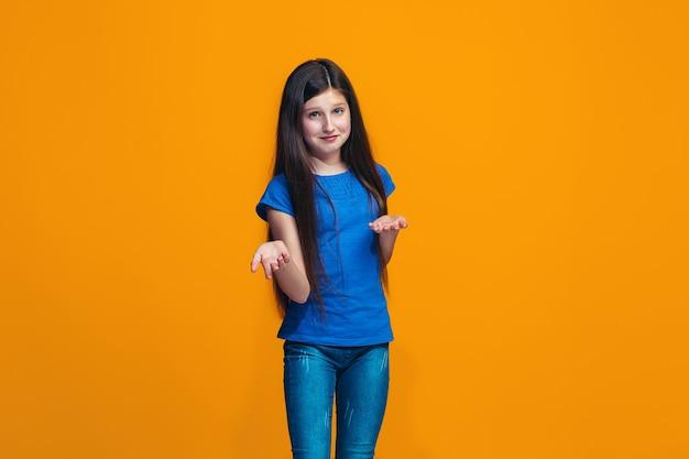 オレンジ色に分離されて驚いて、戸惑う美しい十代の少女