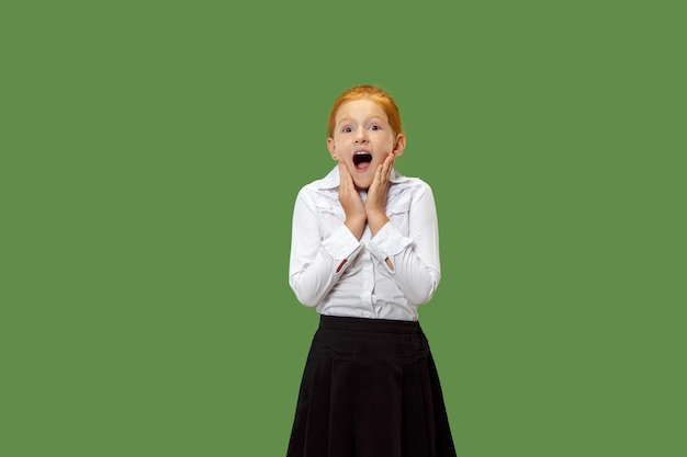 Beautiful teen girl looking suprised isolated on green