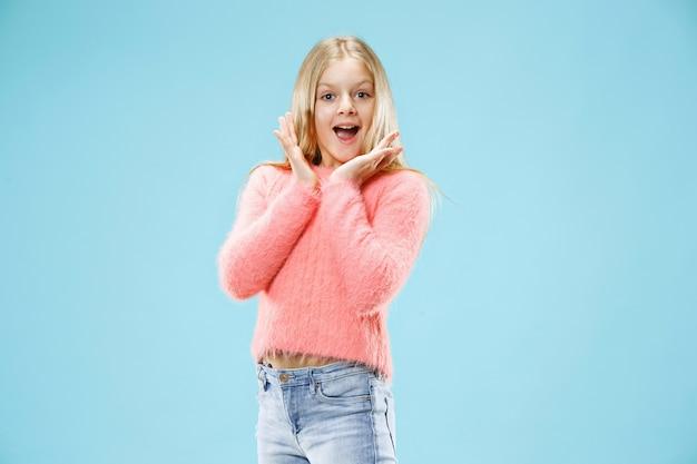 青に孤立して驚いて見える美しい十代の少女