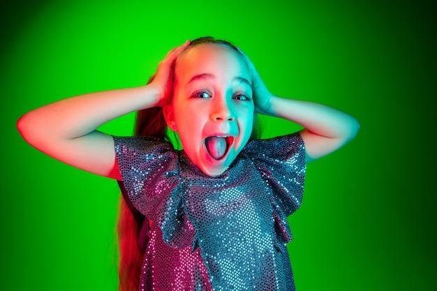 緑に孤立して驚いて見える美しい十代の少女